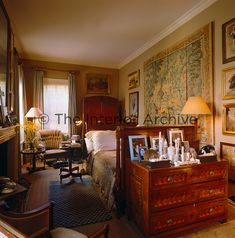 An inlaid chest of drawers with a collection of family photographs and ivory objects stands at the end of the bed in this well furnished bedroom