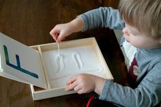 Using a salt tray to practice forming letters. Maybe you could also use sugar, sand, or whatever you can find :)