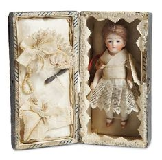 German all-bisque miniature doll, costume, and accessories presented in a paper lace edged candy box trunk with silk lining, for the French market, circa 1900.
