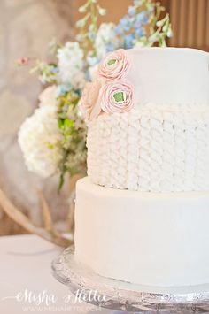 Pretty wedding cake with pink flower accents.