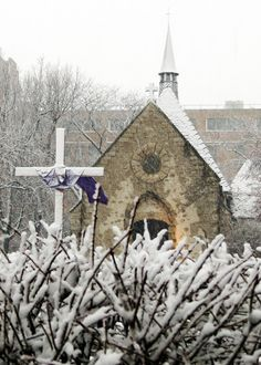 Snow-covered cross at Marquette University's St. Joan of Arc Chapel.