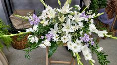 An incredible casket spray with white lilies, purple stock, and more by Field's Floral and Gift