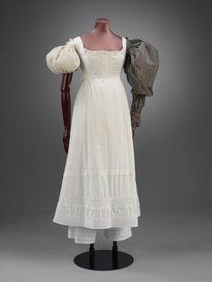 Regency Petticoat 1820 w/support for sleeves. Notice the pantaloons underneath Plain cotton with a double row of piping round the lower part. Frontless with looped shoulder pieces.