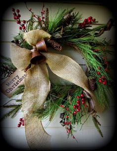 Rustic Christmas Wreath with Burlap Ribbon, Evergreens, Berries & Pinecones; homemade trimmings of any evergreen, live or faux red berries, consignment store old bells and easy burlap bow. Beautiful!