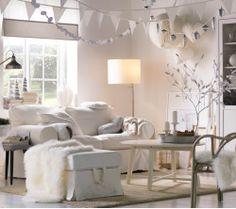 Ein weißes Wohnzimmer geschmückt mit Hängedekorationen und natürlichen Elementen, die zum Winterthema passen, u. a. HOLMSEL Rattansessel in Grau und TEJN Lammfellimitaten in Weiß