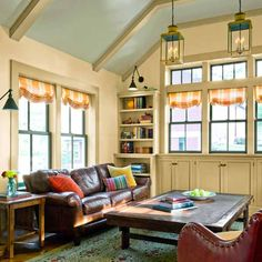 Cabinets under these family room windows hide media components and a flat-screen TV on a motorized lift.