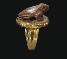 AN EGYPTIAN AGATE FROG   LATE PERIOD TO PTOLEMAIC PERIOD, 664-30 B.C.   Perhaps the lid of a cosmetic vessel, on an oval plinth, naturalistically rendered, the eyes and mouth delineated by incision, pierced horizontally through the chest and stomach; mounted as a ring in a modern gold setting