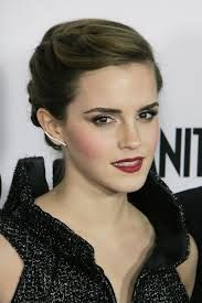A romantic braided updo on actress Emma Watson. The hair is a sophisticated hairstyle with no bangs. She has a very strong natural part slightly to one side and the style looks like a classic updo from the front.