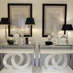 Black and white vignette with architectural prints, crystal lamps, and chrome and glass tables