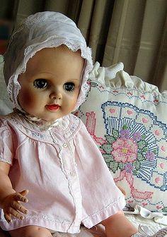 vintage doll wearing vintage pink baby dress , hat , booties