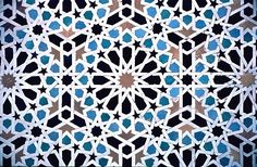 Image MOR 0307 featuring decorated area from the Attarine Medersa, in Fez, Morocco, showing Geometric Pattern and Calligraphy using ceramic tiles, mosaic or pottery.