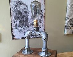 This Steampunk inspired lamp features two 60 watt Edison style bulbs (included), vintage wooden block is welded to the 3/4 inch pipe and is framed by the pipe fittings. Black wire cages protect the bulbs.  This lamp is wired with a generous 6 foot vintage twisted cloth covered power cord.  The blue valve handle acts as the on/off switch.  Other accents include brass faucet, sprinkler head, and pressure gauge.  This is a substantial heavy duty lamp.  Details:  Dimensions: 31 H X 21 W X 7  D…
