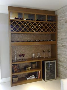 Estante com nichos e prateleiras para vinho e também espaço para embutir uma adega refrigerada. Uso de fundo em cortiça e detalhes em espelho