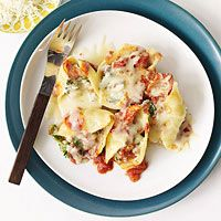 Stuffed Shells    1 pound broccoli rabe, tough stems trimmed, roughly chopped  1 12 ounce box jumbo pasta shells  1 tablespoon olive oil  1 - 1 1/4 pounds spicy chicken sausage, casings removed, crumbled (uncooked)  2 5.3 ounce package Chavrie goat cheese with basil and roasted garlic  4 ounces Neufchatel cheese, softened  2 egg yolks  1 24 ounce jar cabernet marinara sauce  1 8 ounce bag shredded mozzarella