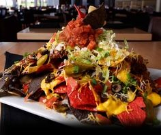 NACHOS Ingredients 12oz chips,8 oz chili,8oz queso sauce,2oz lettuce,2oz jalapeno,2oz black olives, 2oz sour cream,2oz salsa,1/2 oz green onions Put half of the chips on the bottom of a large platter.  2. Top chips w/ 1/2 chili, followed by queso.  3. Top with remaining chips and follow with remaining chili+queso. 4. Top chili with black olives, japs, lettuce. 5. Top lettuce with sour cream+salsa, followed by green onions. 6. Top entire plate with one red, blue chip, white chip.