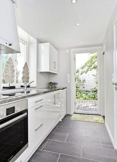 Grey slate floor tiles with white glossy kitchen