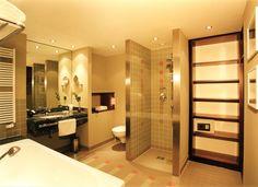 Warme harmonische Farben und eine zeitlose Atmosphäre erwarten Sie beim Einritt in unsere Zimmer und Junior-Suiten.    Die großzügigen Bäder mit Panorama Spiegel, bodenebene Duschen mit einer Sitzbank aus brasilianischem Granit tragen ebenso zum Wohlfühlen bei, wie die Fußbodenheizung, der Handtuchtrockner und die vielfältigen Ablagen. Das Hotel, Bad, Bathroom Lighting, Bathtub, Mirror, Furniture, Home Decor, Showers, Banquette Bench