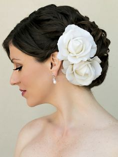 Real feel rose flower bridal hair clip in a curly bridal updo by Hair Comes the Bride.