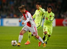Lasse Schone of Ajax is tackled by Rafinha of Barcelona during the UEFA Champions League Group F match between AFC Ajax and FC Barcelona at The Amsterdam Arena on November 5, 2014 in Amsterdam, Netherlands.
