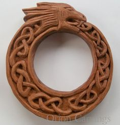 Woodcarving representing an Ouroboros, depicting a dragon eating its own tail. Handmade woodcarving made in a native chilean wood called rauli (Nothofagus alpina). It measures 6,8 x 1,4 in (17 x 3 cms).