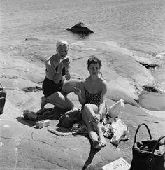 Naisia paistattelemassa päivää meren rannalla. Kuva: Helsingin kaupunginmuseo / Volker von Bonin, 1952.