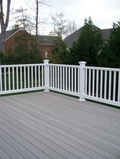 A grey solid color stain on this deck looks great with the white railing and posts. Two-color combos look fantastic on decks. For deck finishing in Bellingham WA, visit www. Grey Deck Stain, Deck Stain Colors, Deck Colors, Decking Colours Ideas, White Deck, Black Deck, Gray Deck, Outdoor Deck Decorating, Deck Railings