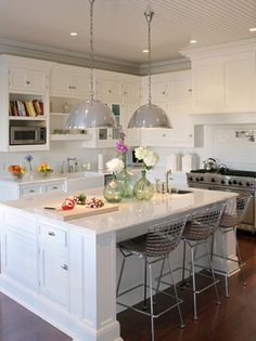 Antique industrial lamps and Bertoia chairs in Hampton kitchen by KTS interiors