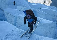Crossing a crevasse at Khumba Icefall, Mount Everest.