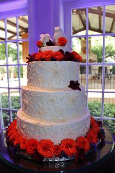 White wedding cake with orange roses and purple orchids. Rockwall Wedding Chapel www.rockwallchapel.com