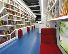 The adventure area inside a German bookmobile. It features free-form shelving and bright colors. Im just glad I dont have to shelve the books!