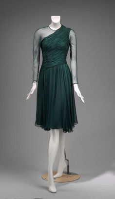 Dark green silk chiffon rounded neckline, short dress with diagonally shirred bodice and long sleeves with side vents and two metal snaps on each sleeve. Bow on right shoulder seam. Gathered skirt with diagonal waistline. Hidden zipper going from the side of the bodice to the back of the dress at the right shoulder with one snap closure. Lined in dark green silk, zipper has a metal weight inside of the dress at the side.