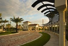 Palm Beach Gardens, Florida. Dramatic curved metal panels shelter a winding walkway. A brick and stone paved road leads past palm trees to the gated entry of the Paloma new home community. Homes by Kolter Homes.
