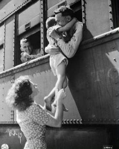 Wife of a departing soldier lifts son for farewell embrace. Oklahoma, 1945.