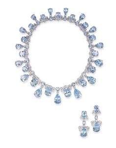 A SUITE OF TOPAZ AND DIAMOND JEWELRY  Comprising a necklace, composed of a graduated series of oval-cut blue topaz surmounted by circular-cut diamond ribbon bow motifs, spaced by a circular and pear-shaped blue topaz fringe, enhanced by circular-cut diamonds; and a pair of ear pendants en suite, mounted in 18k white gold