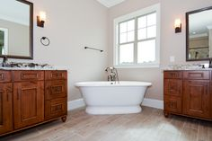 """RUSTIC ALDER cabinets in Harvest stain with black glaze, Exodus White granite, Kingsley faucet from Moen, """"wood"""" tile floor, and York free-standing tub from Victoria & Albert"""