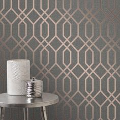 A trellis design wallpaper from Fine Decor's best-selling Quartz range in a modern, geometric style in a shimmering rose gold on a charcoal textured background that has a silver glitter effect throughout.
