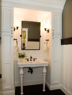 This traditional bathroom features custom white cabinetry that flanks a freestanding console sink. A pivot mirror hangs over the sink, while sconces in oil-rubbed bronze light up and add elegance to the space.