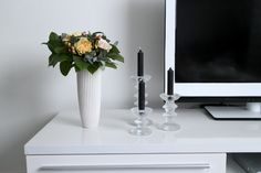 Flowers and candles (Iittala Festivo) on TV stand.  Koti-ikävä ja matkakuume.