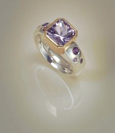 Ring; Sterling silver, with pale amethyst set in 9ct gold and flush set amethysts on the shoulders. One of a kind.