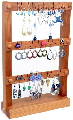This wooden jewelry holder - earring holder is compact and will look wonderful holding all of your earrings while not taking up too much dresser space. This earring holder has holes to cleanly hold 15 pairs of earrings and slots to cleanly hold another 15 pairs (30 pairs total). Capacity will vary depending on how big your earrings are and what types of earrings you have.  Please visit my shop: http://www.etsy.com/shop/TomsEarringHolders  Wood: Cherry Finish: Coated with liquid beeswax to…