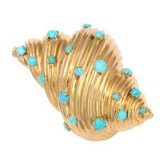 Tiffany-Paris. A three dimensional, spiraling shell of glittering 18K gold, studded with cabochons of Persian turquoise. 1 1/2 in x 2 1/4 in. French gold marks and Tiffany EC France.Ca. 1950s