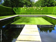 Water Garden at Kiftsgate Court, Gloucestershire - a modern masterpiece commissioned by the present owners, where 24 swaying bronze leaves designed by sculptor Simon Allison reflect in the black water of the rectangular pond, complete with stepping stones inspired by the moat at Sutton Place