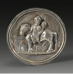 Roman silver roundel with relief showing the goddess Epona riding to the left holding patera and cornucopia, 2nd century A.D. A tiny foal accompanies the mare. Slightly bent, otherwise intact. The piece originally decorated the inside of a silver dish, 8.4 cm diamater. Private collection