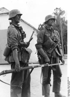 Dos soldados alemanes en la URSS, verano de 1941. El más cercano lleva un fusil Kar 98K con bayoneta calada, y el otro sostiene vagamente por la correa un subfusil MP-40 con la culata desplegada
