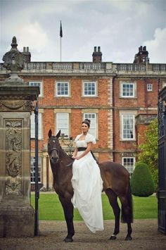 This looks like a traditional English Country Estate.It has the fall stone wall with iron gates.The beautiful lady in the lavish white gown is riding side saddle on such a gorgeous Horse.This last part of the image is the giant Cherry on the Sundae.