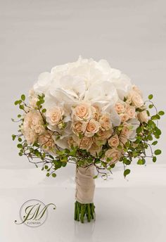 White hydrangeas surrounded with spray pale peach roses finished with fine twigs. Pastel, romantic Bridal Bouquet.