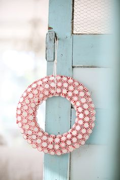pretty candy cane wreath - no tutorial but can DIY by using white styrofoam wreath & gluing on peppermint candies