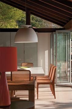 A luminária de cerâmica vermelha vem da Santa Maria Casa e o pendente Bossa sobre a mesa de jantar é da Lumini. Móveis de proporções bem definidas permitem a boa circulação.