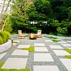 Fireproofed & Lawnless: A patio of bluestone pavers, crushed rock, and low groundcovers, edged with a sinuous concrete seat wall—and contained fire burns in a custom firepit of Cor-ten steel. Crushed drain rock adds a contemporary edge to bluestone pavers. Groundcovers of Irish moss, creeping thyme, and chamomile soften the rock.