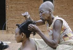 Africa | The photograph depicts old woman doing traditional hairstyle on Mbombio, Chief Mogendo's principal wife. | The funnel-shaped coiffure which ended in an outward halo, originally symbolic of high social status, was considered exceptionally attractive, and took a lot of time to create.  | ©Eliot Elisofon.  1970